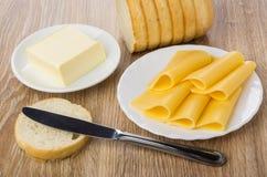 Plakken van kaas, brood, stuk van boter in schotel, mes Stock Foto's