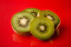Plakken van kiwifruit op rode achtergrond, horizontaal schot royalty-vrije stock fotografie