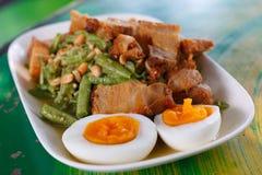 Plakken van knapperig varkensvlees en gekookt ei op Yardlong-boonsalade Stock Foto's