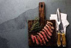 Plakken van middelgroot zeldzaam rundvleeslapje vlees op houten raad, uitstekend snijdend bestek stock foto