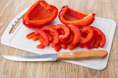 Plakken van paprika en keukenmes Stock Foto's