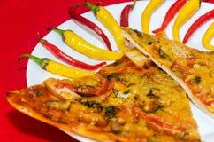 Plakken van pizza op plaat met gele en Spaanse pepers Stock Afbeeldingen