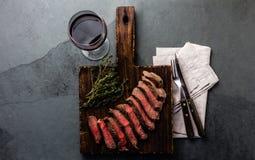 Plakken van rundvlees middelgroot zeldzaam lapje vlees op houten raad, glas rode wijn stock foto's