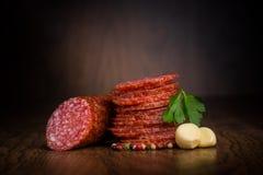 Plakken van salami op een houten lijst Stock Foto's