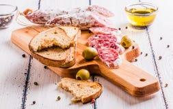Plakken van salami op een scherpe raad Stock Fotografie