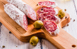 Plakken van salami op een scherpe raad Royalty-vrije Stock Afbeeldingen
