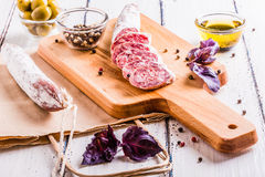 Plakken van salami op een scherpe raad Stock Afbeelding