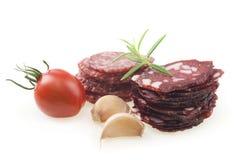 Plakken van salami op een witte achtergrond wordt geïsoleerd die Royalty-vrije Stock Foto's