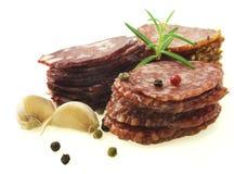 Plakken van salami op een witte achtergrond wordt geïsoleerd die Stock Foto's