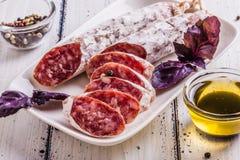 Plakken van salami op een witte plaat Royalty-vrije Stock Afbeelding