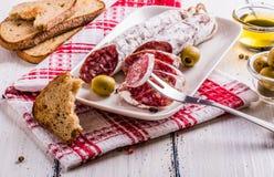Plakken van salami op een witte plaat Stock Afbeeldingen