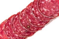 Plakken van salamiworst op een witte achtergrond Stock Afbeeldingen