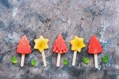 Plakken van watermeloen in de vorm van Kerstbomen op een stok Plakken van perzik in de vorm van een ster op een stok Fruit op st royalty-vrije stock afbeeldingen