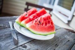 Plakken van watermeloen en een mes op een plaat op een houten backgrou Stock Foto