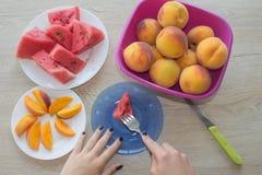 Plakken van watermeloen en perziken op een plaat op de houten lijst Organische Rijpe Zaadloze Watermeloen en perzikenbesnoeiing i Stock Foto's