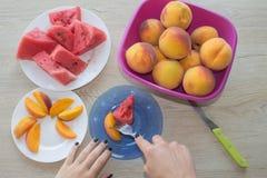 Plakken van watermeloen en perziken op een plaat op de houten lijst Organische Rijpe Zaadloze Watermeloen en perzikenbesnoeiing i Stock Afbeeldingen