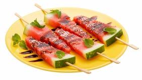 Plakken van watermeloen met stok op gele plaat op whit Royalty-vrije Stock Foto's