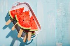 Plakken van watermeloen op blauw houten bureau Stock Foto