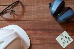 Plakte veiligheids eerste nota één geel stuk van document op houten achtergrond met volledige reeks van persoonlijk beschermingsm stock afbeeldingen