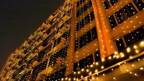 Plam świateł żarówki smyczkowy obwieszenie na budynek ścianie przy nocą, Lekki bokeh drutu obwieszenie i światło, odbijamy w okno fotografia stock