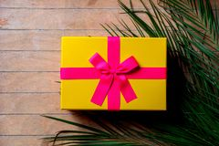 Plam branch and holiday gift box. On wooden table royalty free illustration
