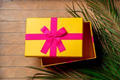 Plam branch and holiday gift box. On wooden table royalty free stock photography