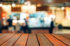 Plama wizerunku drewna stół na zakupy centrum handlowym i ludzie z bokeh Obraz Stock