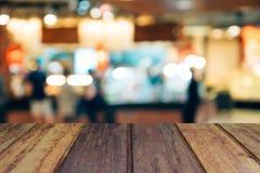 Plama wizerunku drewna stół na zakupy centrum handlowym i ludzie z bokeh Zdjęcie Stock