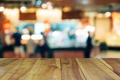 Plama wizerunku drewna stół na zakupy centrum handlowym i ludzie z bokeh Zdjęcia Royalty Free