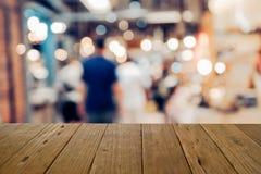 Plama wizerunku drewna stół na zakupy centrum handlowym i ludzie z bokeh Fotografia Royalty Free