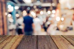 Plama wizerunku drewna stół na zakupy centrum handlowym i ludzie z bokeh Obrazy Stock