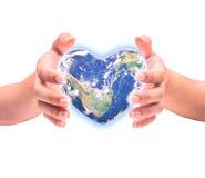 Planète bleue dans la forme de coeur au-dessus des mains humaines de femme d'isolement Photos stock