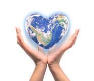 Planète bleue dans la forme de coeur au-dessus des mains humaines de femme d'isolement Photo stock
