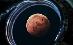 Planète de Mars dans le hublot de fenêtre de vaisseau spatial Éléments de cette image meublés par la NASA photos stock