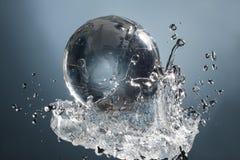 Planète en verre de globe dans l'éclaboussure de l'eau de baisse sur le fond bleu Photographie stock libre de droits