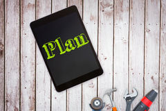 Plan against tools and tablet on wooden background Royalty Free Stock Image
