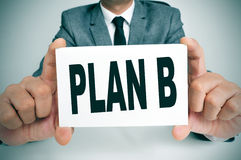 Plan B. Businessman sitting in a desk showing a signboard with the text plan B written in it Royalty Free Stock Photos