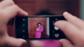 Plan big guy takes on smartphone Woman in black hat and pink coat stock footage