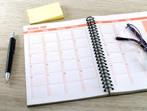 Plan book, pen, glasses and Sticky notes on wood Royalty Free Stock Image