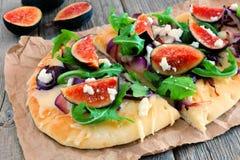 Plan brödpizza med fikonträd, arugula, getost, över trä Royaltyfri Fotografi