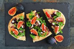 Plan brödpizza med fikonträd, arugula, ost, fast utgift kritiserar på Fotografering för Bildbyråer