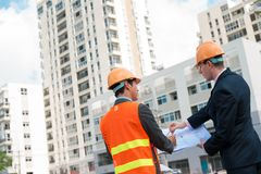 Plan of the building. Architect and client discussing the plan of the building at the construction site, rear view Royalty Free Stock Images