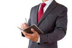 Plan d'écriture d'homme d'affaires avec le stylo et le bloc-notes photo stock