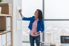Plan de jour d'écriture de planification de jeune femme sur le panneau blanc, marqueur de participation dans la main droite Photos stock