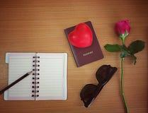 Plan de la tarjeta del día de San Valentín del viaje del concepto: pluma en el cuaderno abierto, pasaporte, imagen de archivo