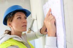 Plan de lecture d'architecte de femme sur le chantier de construction Photographie stock