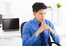 Plan de pensamiento del hombre de negocios joven en la oficina imagen de archivo libre de regalías