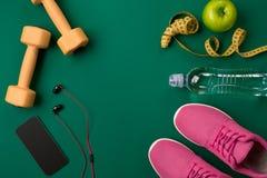 Plan de séance d'entraînement avec la nourriture et l'équipement de forme physique sur le fond vert, vue supérieure Photographie stock libre de droits