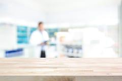 Plan de travail en bois vide sur le fond de pharmacie de tache floue Photos libres de droits