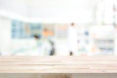 Plan de travail en bois vide sur le fond de pharmacie de tache floue Photographie stock